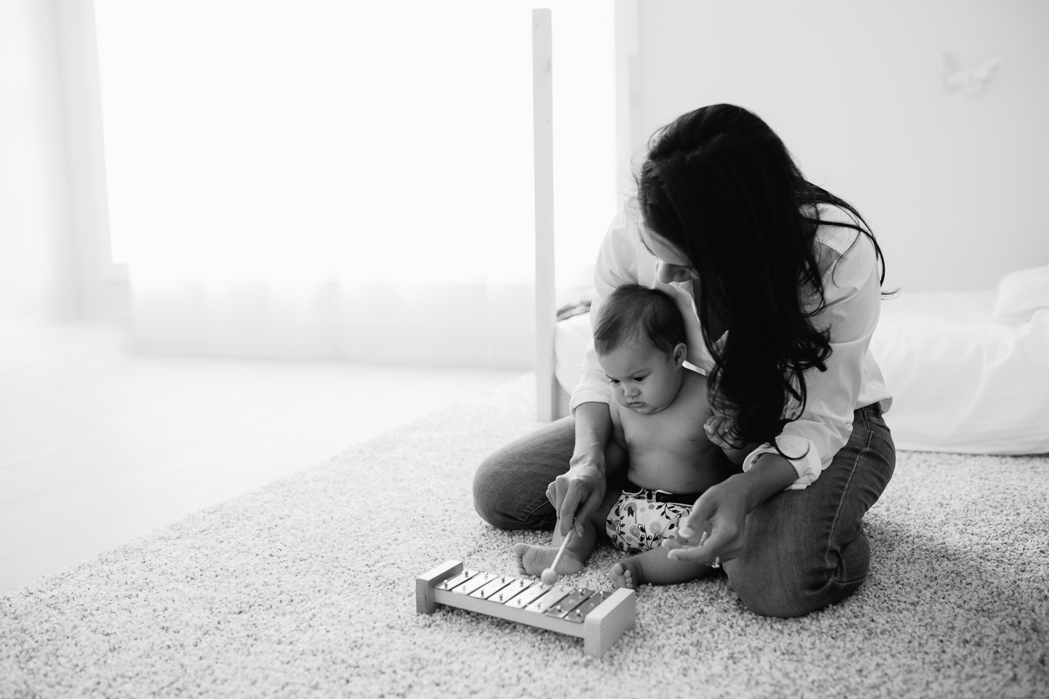 mother and 6 month old baby daughter sitting on floor playing with xylophone - Stouffville In-Home Photography