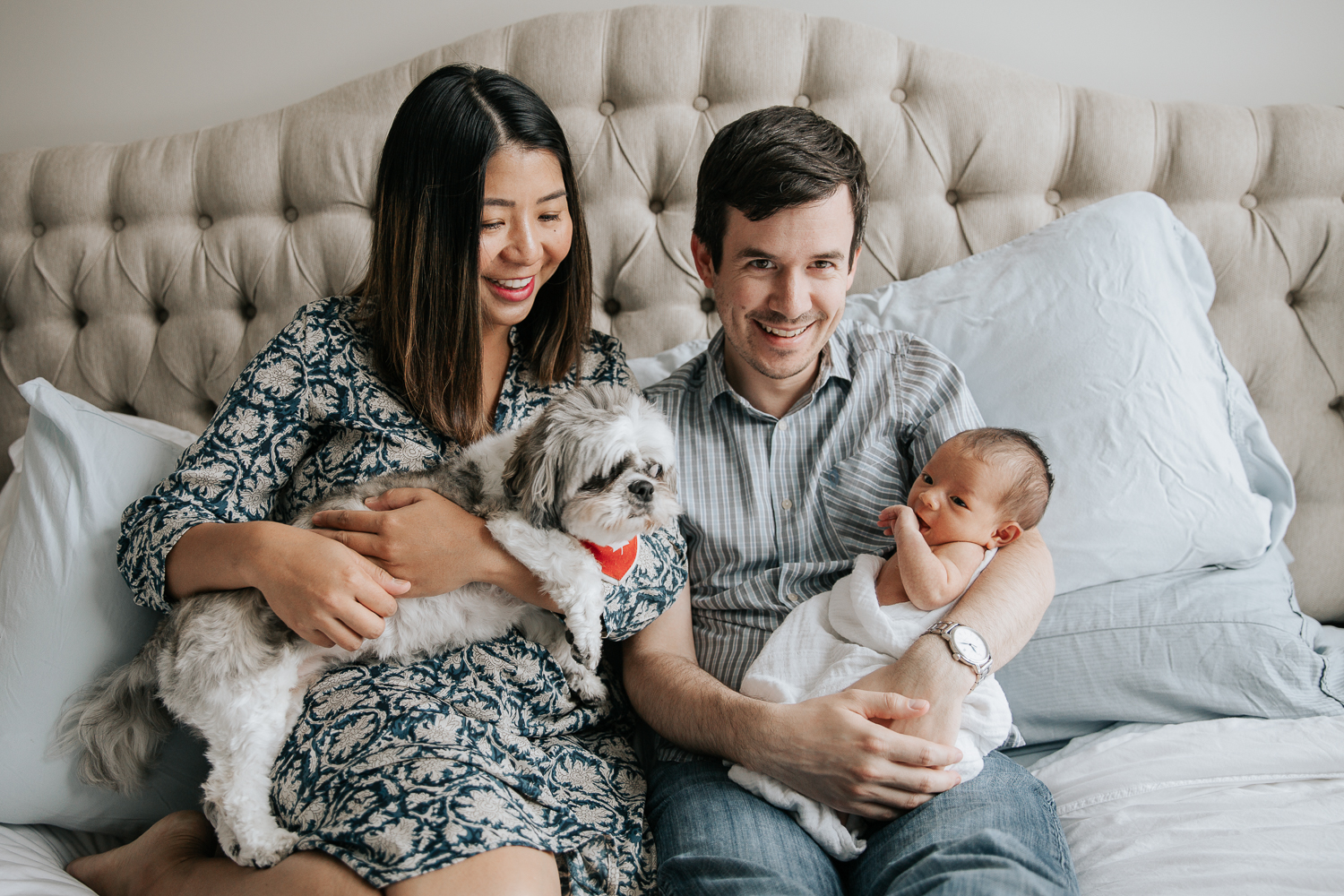 new parents sitting on master bed holding 2 week old baby girl and shitzu dog - Barrie Lifestyle Photography