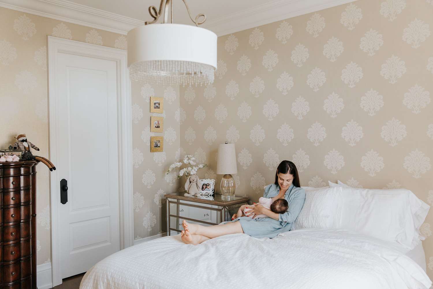 new mom with dark hair in blue chambray dress sitting on master bed, nursing and smiling at 2 month old baby girl in her arms - Stouffville In-Home Photography