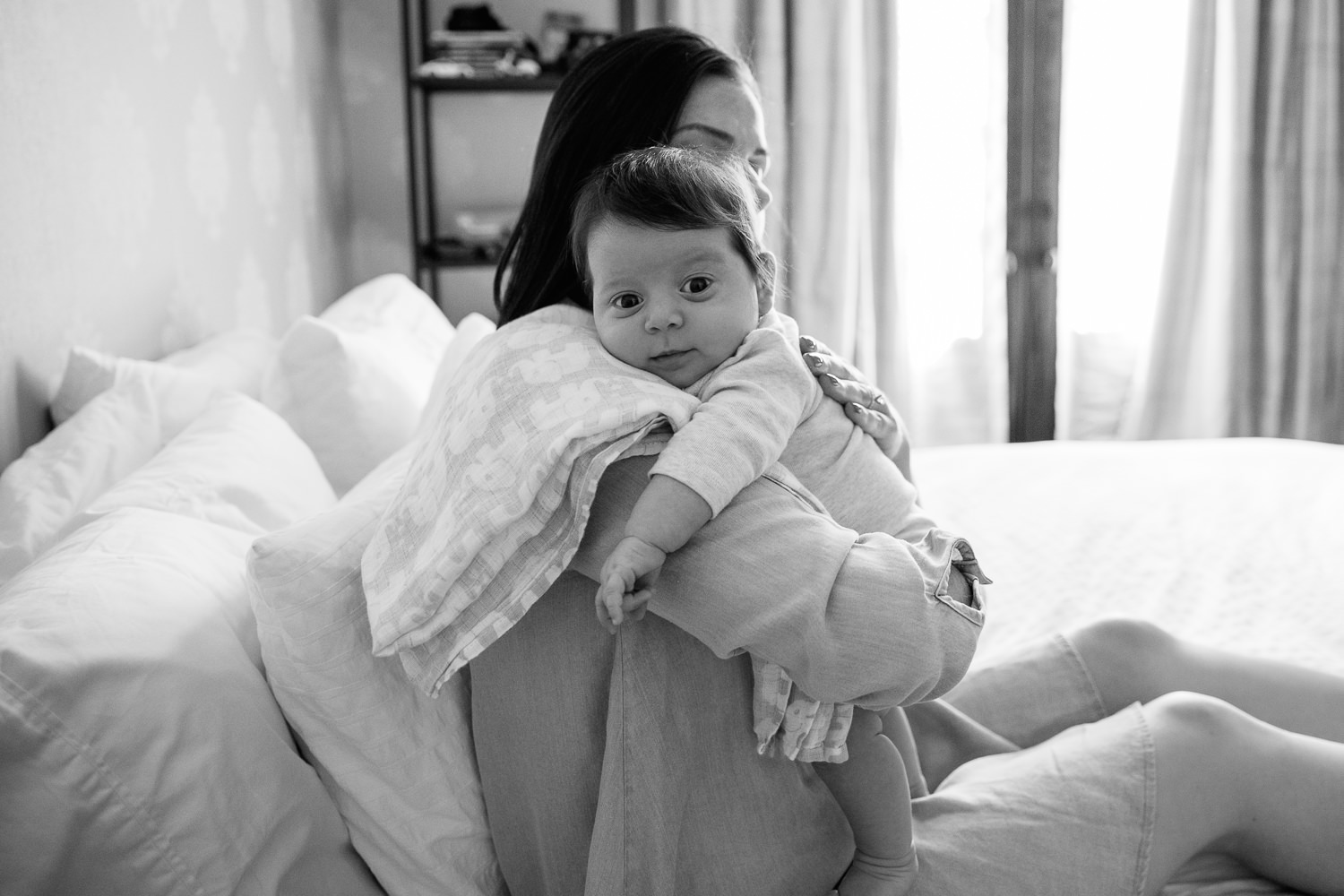 new mom with dark hair in blue chambray dress sitting on master bed, holding 2 month old daughter over her should, burping her, as baby girl looks at the camera - Markham In-Home Photography