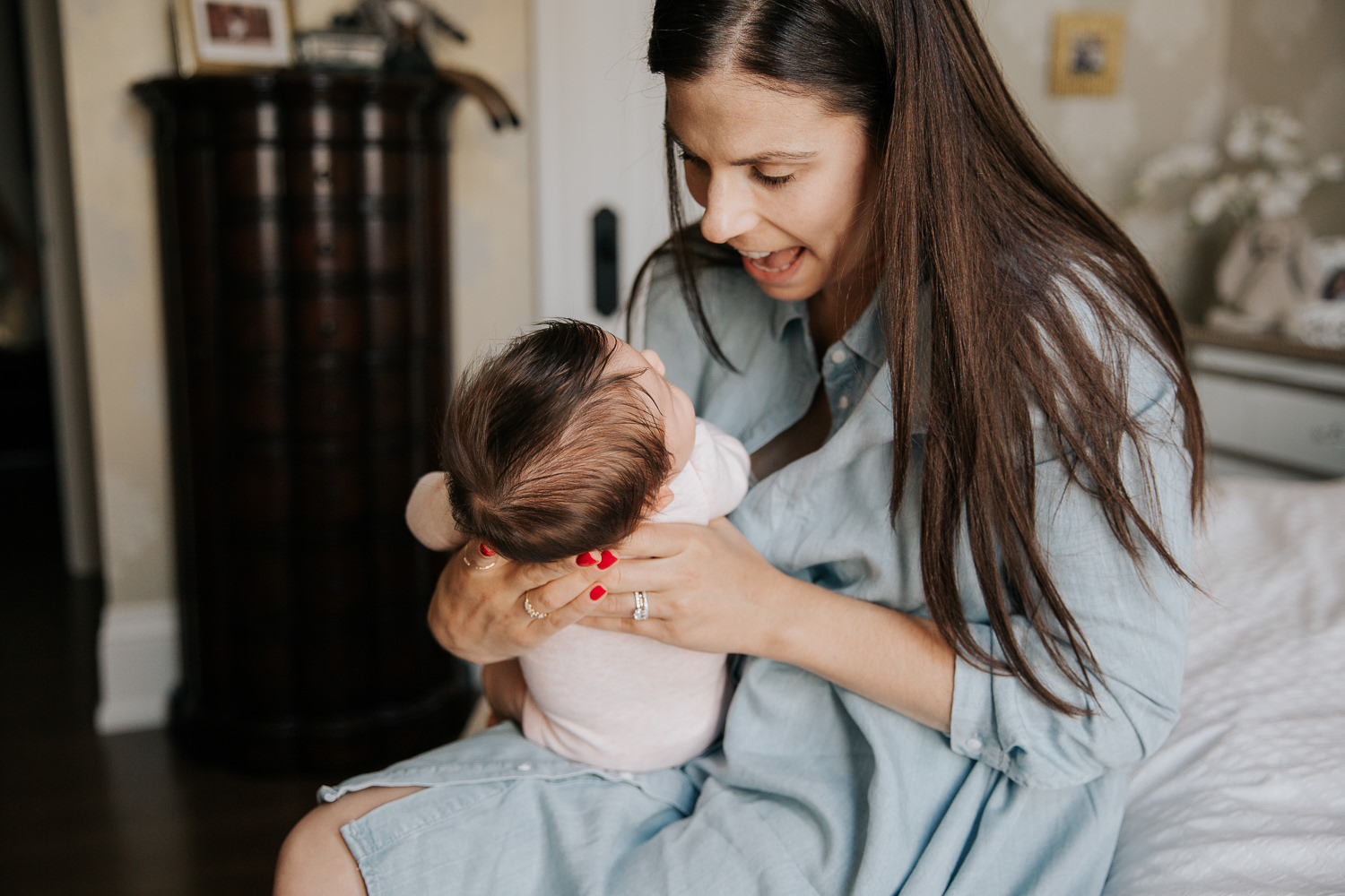 first time mother with long brunette hairin blue chambray dress sitting on master bed, smiling at 2 month old baby girl in pink onesie her arms - Markham In-Home Photos