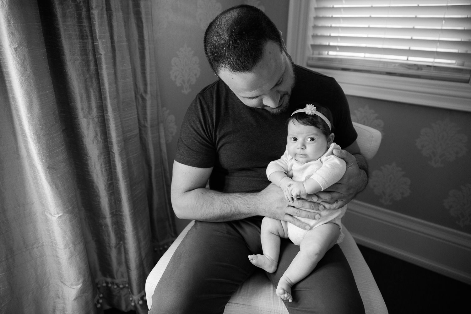 new dad in jeans and t shirt sitting in chair holding and smiling at 2 month old baby girl in onesie who is sitting on his knee looking at the camera -  GTA In-Home Photos