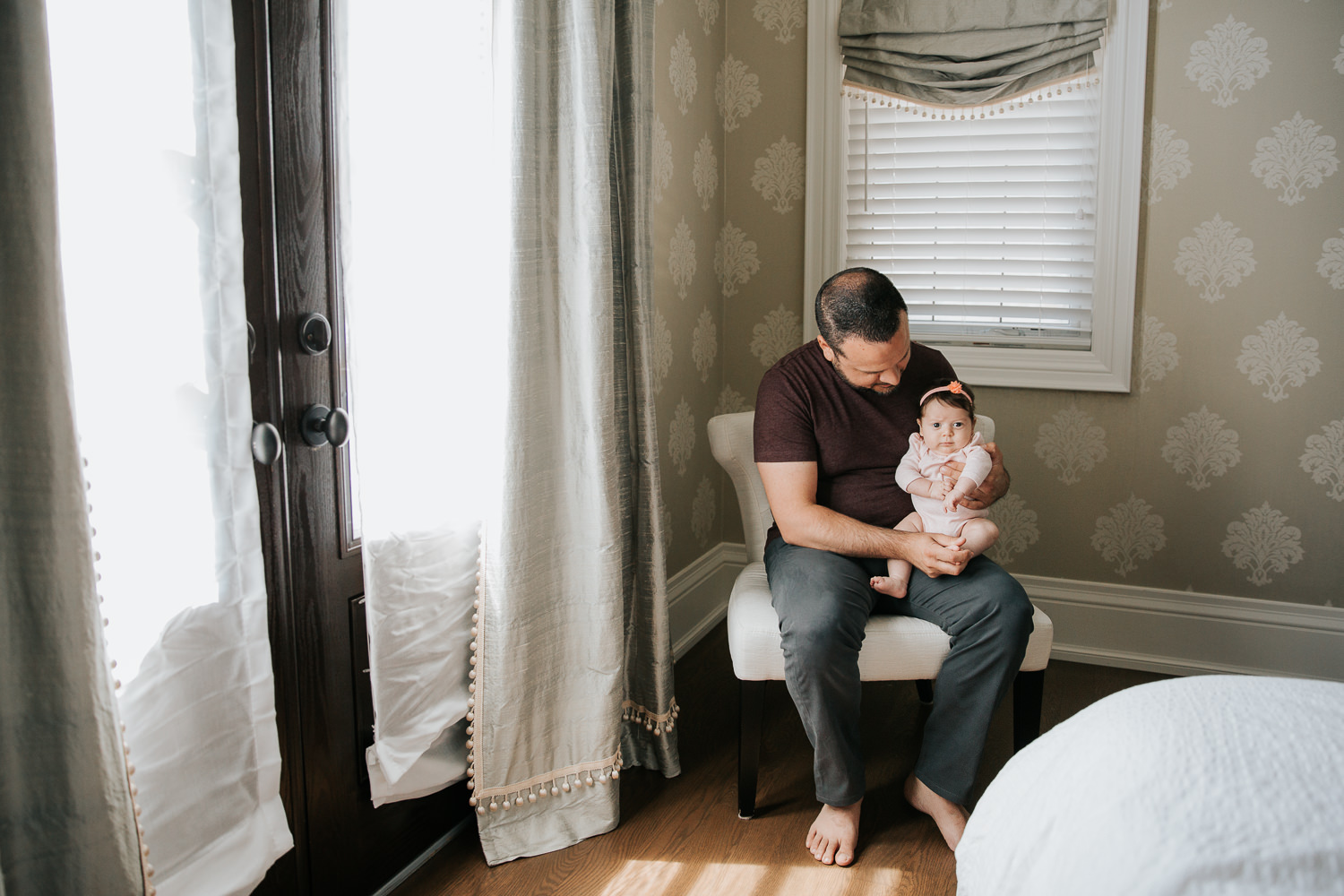 new dad in jeans and t shirt sitting in chair holding and smiling at 2 month old baby girl in pink onesie who is sitting on his knee looking at the camera -  Newmarket Lifestyle Photos