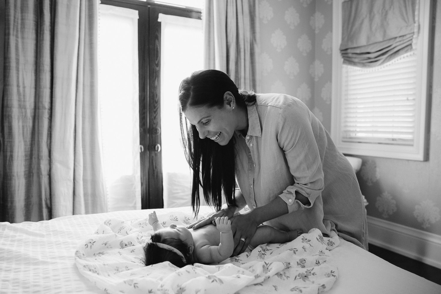 new mom with long brunette hair in chambray dress leans over 2 month old baby girl as she changes her diaper - Stouffville Lifestyle Photos