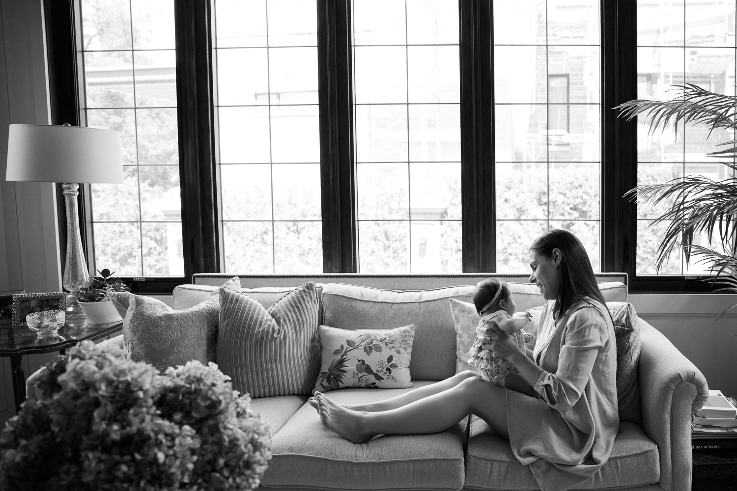 new mom sitting in front of wall of windows with feet up on couch holding and smiling at 2 month old baby girl - Barrie In-Home Photos