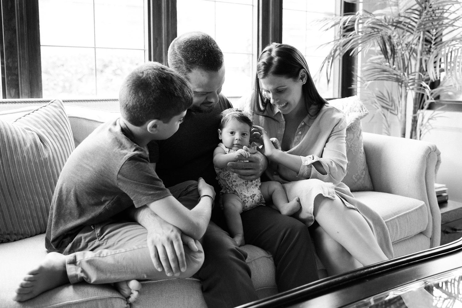 family of four sitting on couch, mom, dad and 9 year old son looking at 2 month old baby daughter in father's lap - Barrie Lifestyle Photos