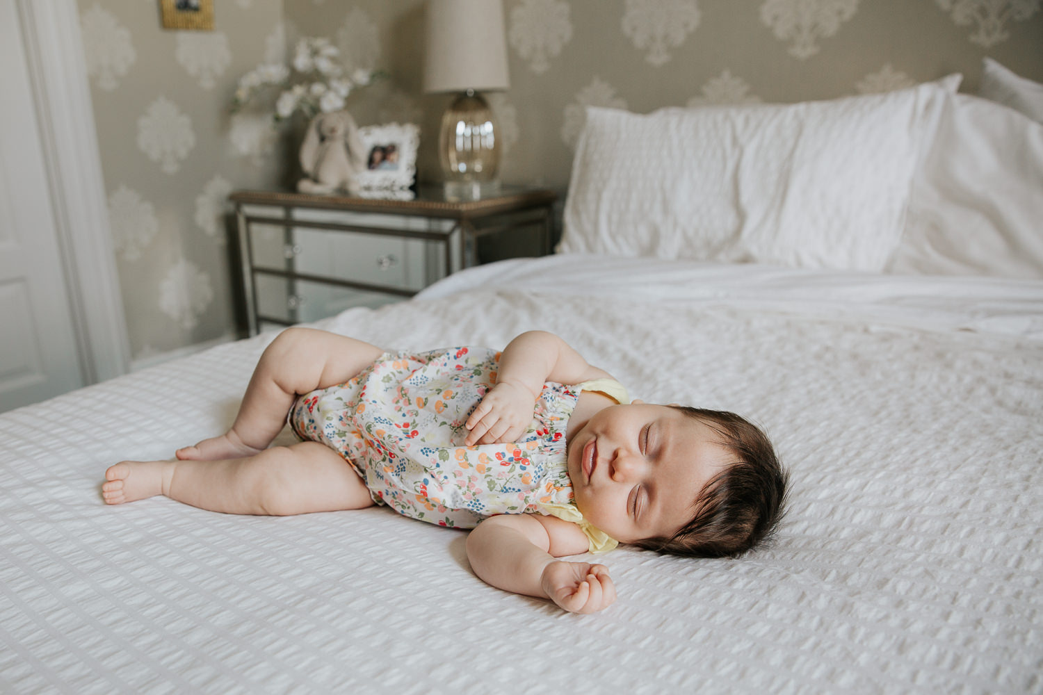 2 month old baby girl with lots of dark hair in floral jumper asleep on bed with arm stretched out - Barrie Lifestyle Photography