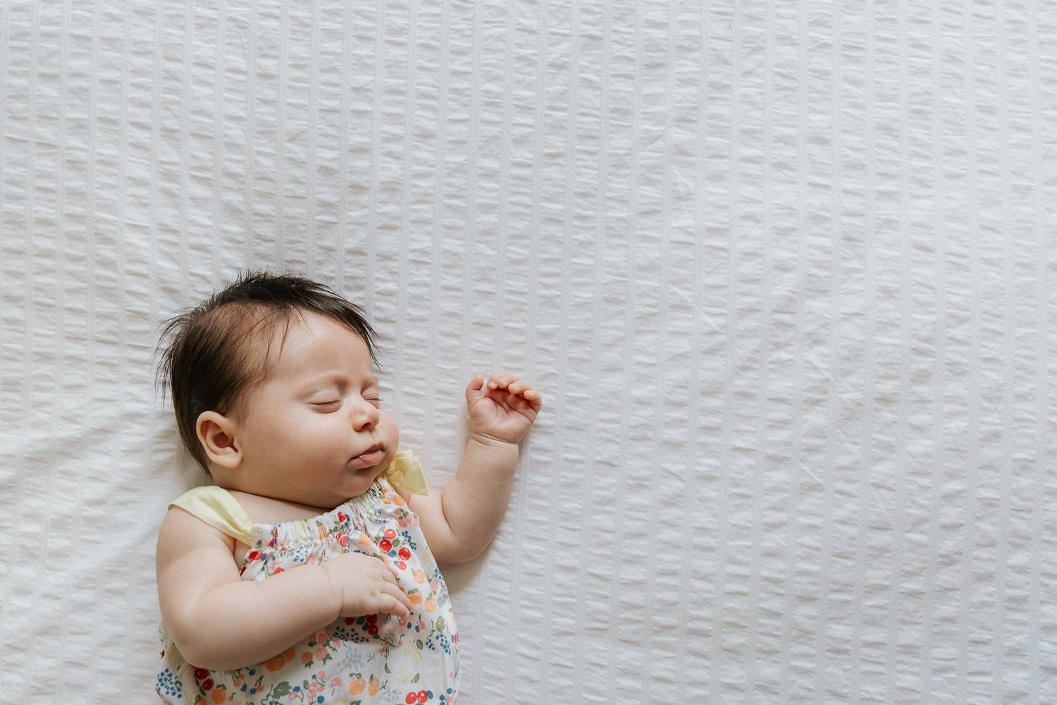 2 month old baby girl with lots of dark hair in floral jumper asleep on bed with arm stretched out - GTA Lifestyle Photography