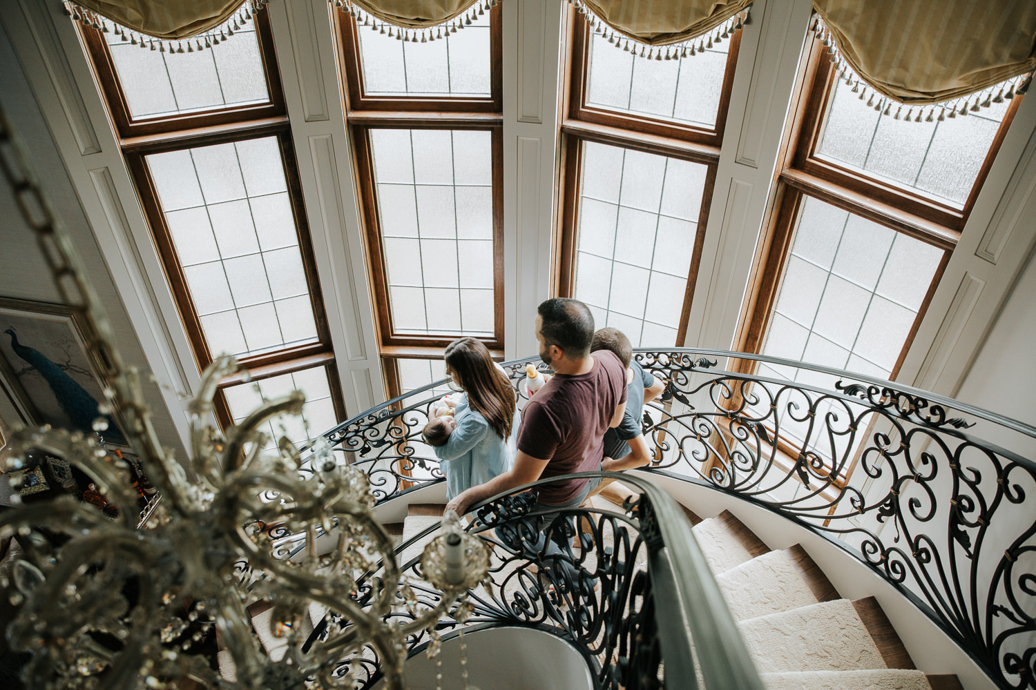 family of four walking down curved, ornate staircase, mom holding 2 month old baby girl, dad and 9 year old brother walking behind - Markham Lifestyle Photography