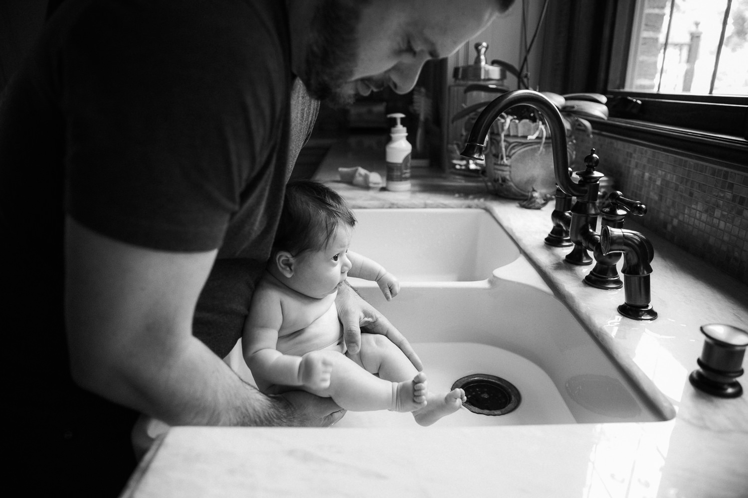 father putting 2 month old baby girl into the kitchen sink for bath time - GTA Lifestyle Photography
