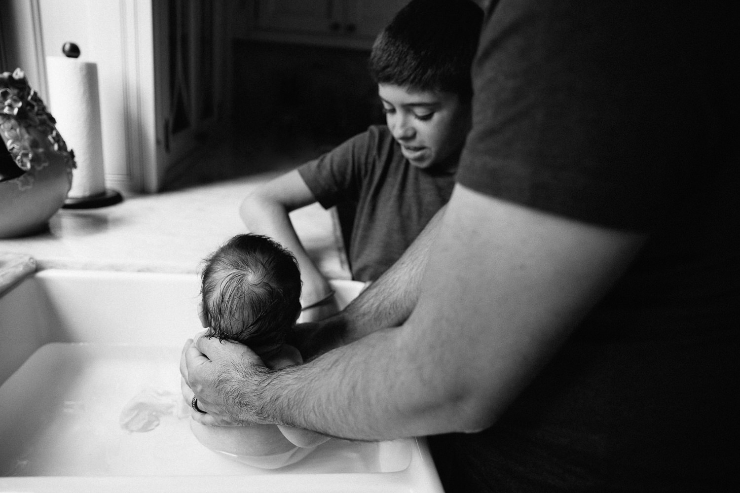 2 month old baby girl with lots of dark brown hair in kitchen sink getting a bath from dad and 9 year old big brother - Barrie In-Home Photography