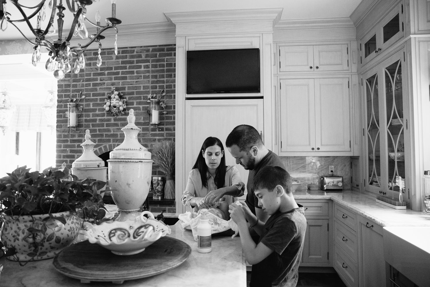 mom, dad and 9 year old brother standing around kitchen island drying off and dressing 2 month old baby girl after her sink bath - Stouffville In-Home Photos