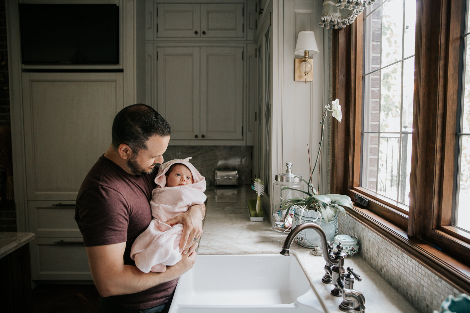 father standing next to kitchen sink, holding 2 month old baby girl wrapped in pink hooded towel after her bath - Markham In-Home Photos