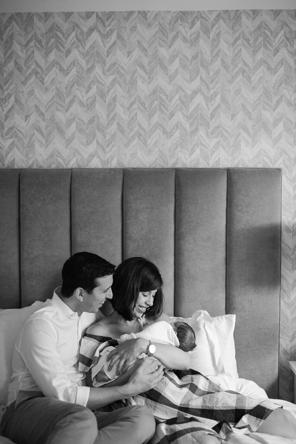 new parents sitting on master bed, mom holding 2 week old baby boy with dad sitting next to them - Barrie In-Home Photos