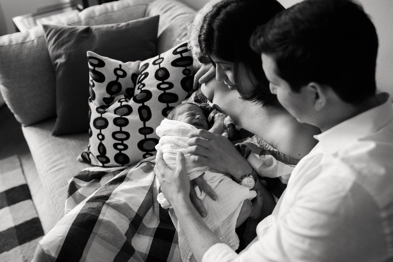 new parents sitting on couch in living room snuggling 2 week old baby boy in white swaddle, mom holding son, dad with arm around her - Newmarket In-Home Photos