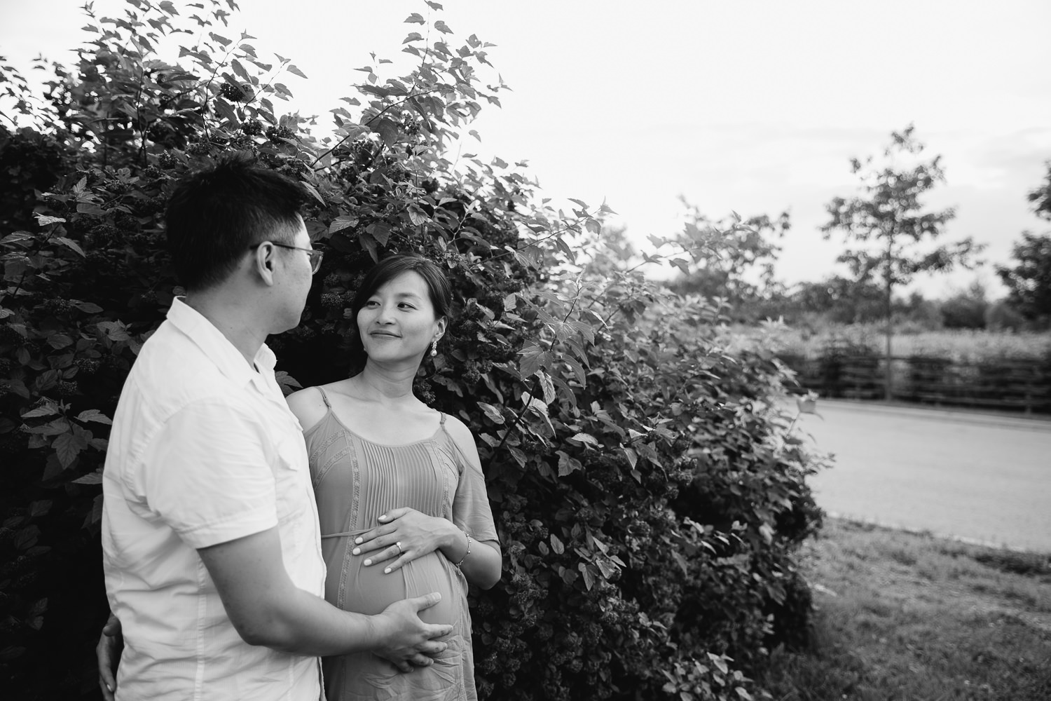 pregnant woman with brunette hair wearing coral top standing with and looking at husband, both resting hands on her baby bump - Newmarket In-Home Photos