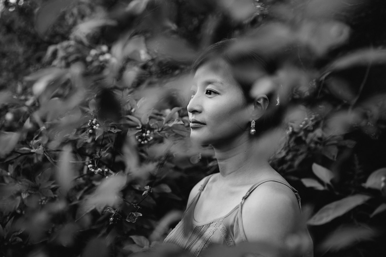 brunette woman with hair up in clip, wearing dangly earrings and a tank top looking off into the distance, shot through foliage - Markham In-Home Photos
