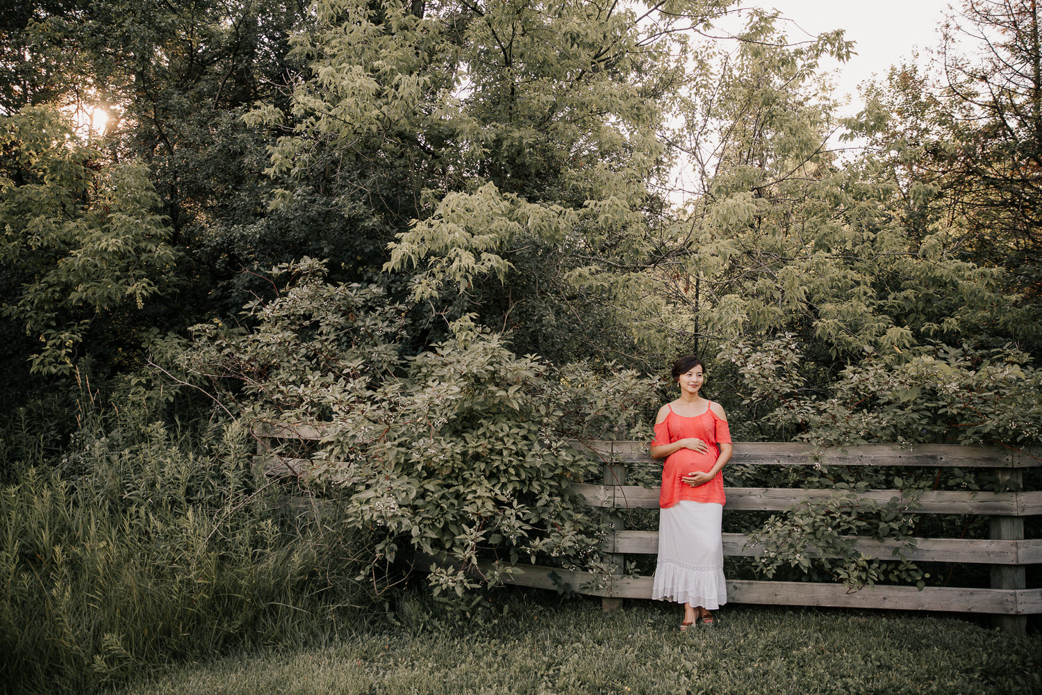 golden hour, pregnant woman in flowy coral top and white skirt leaning against wooden fence holding baby bump as sunlight filters through the trees behind her - GTA In-Home Photos