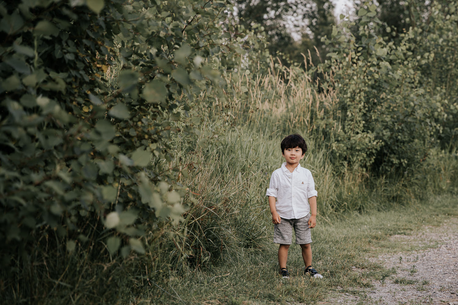 3 year old boy with dark hair wearing white shirt and grey shorts standing next to long green grasses and smirking at camera  -Barrie Lifestyle Photography