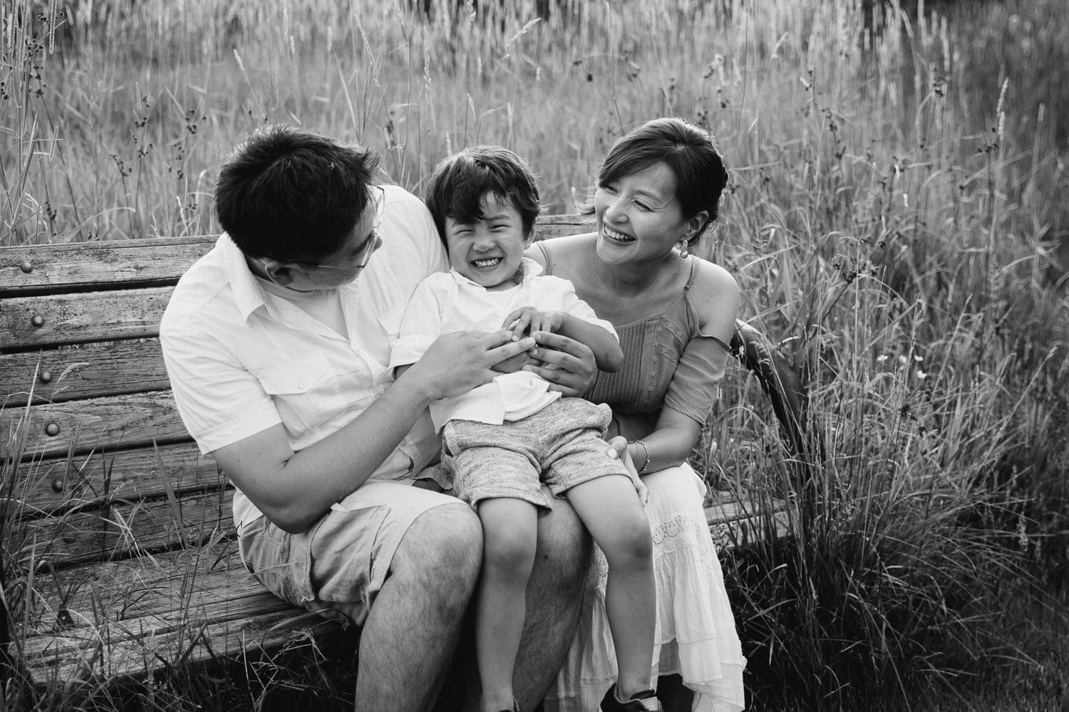 family of 3 sitting on bench park, toddler boy sitting on parent's laps and laughing as dad tickles him - Markham In-Home Photography