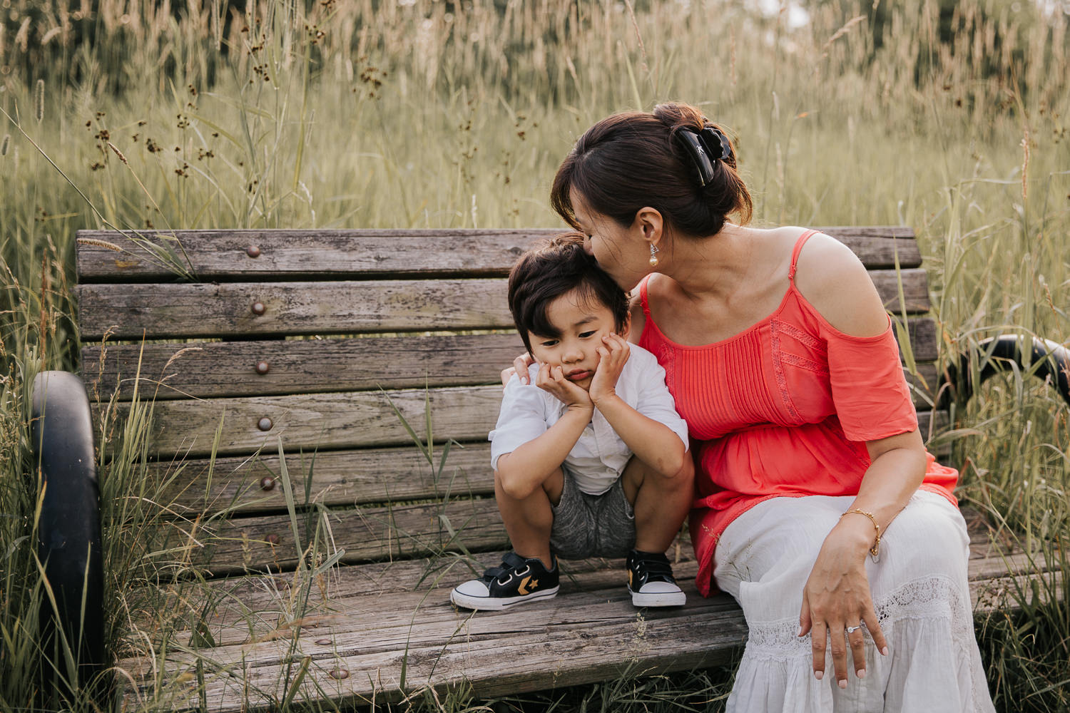 3 year old toddler boy squatting on bench with head in hands and a sad face, mom sitting next to him, leaning over and kissing son's head - Barrie In-Home Photography