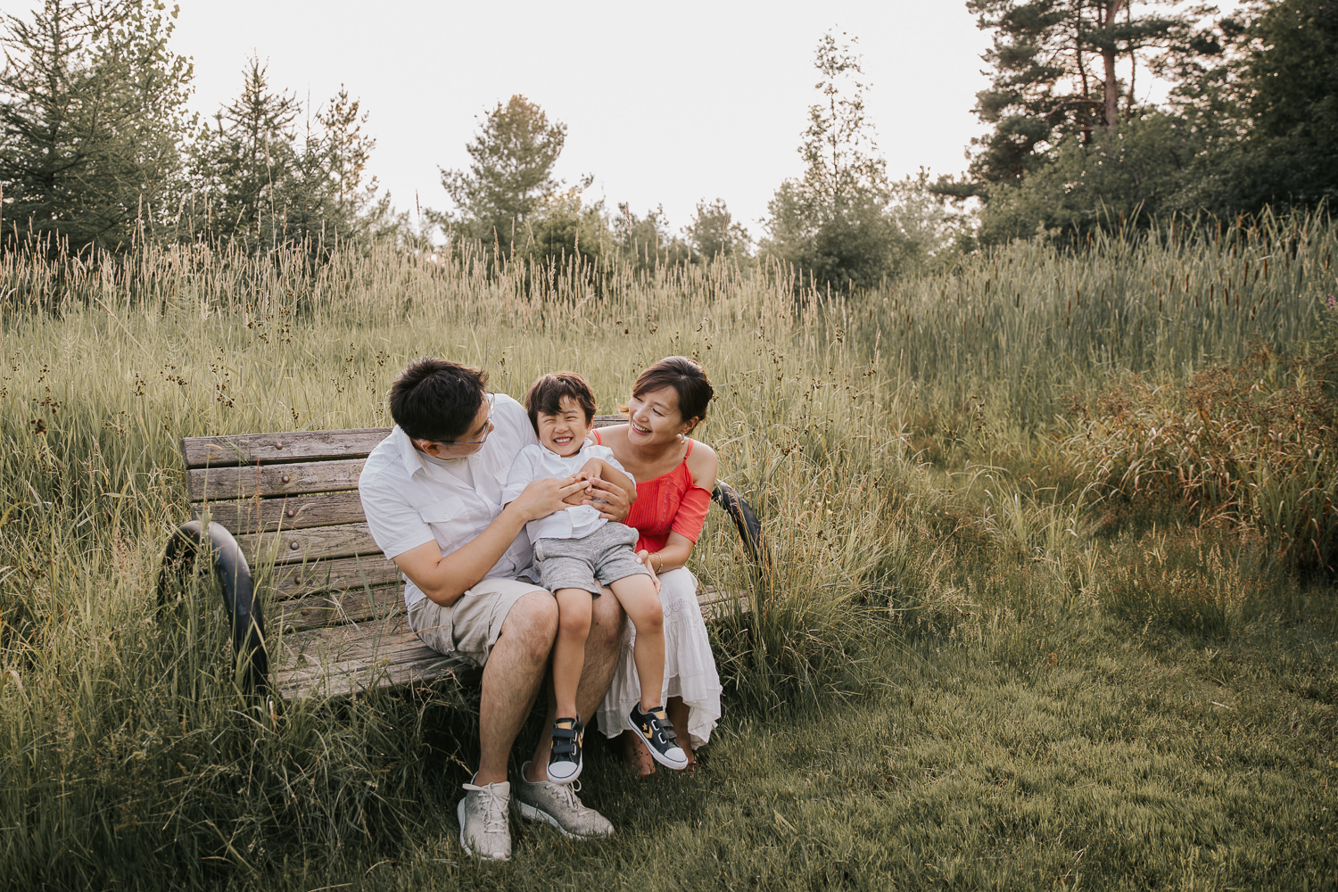 family of 3 sitting on bench park, toddler boy sitting on parent's laps and laughing as dad tickles him - Stouffville In-Home Photography