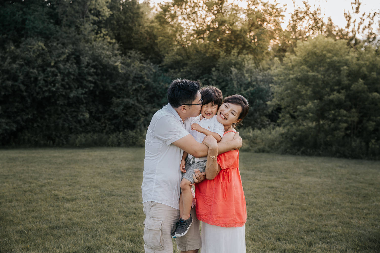 family of 3 standing in park, mom and dad embracing 3 year old toddler son between them, dad kissing boy on cheek - Markham In-Home Photos