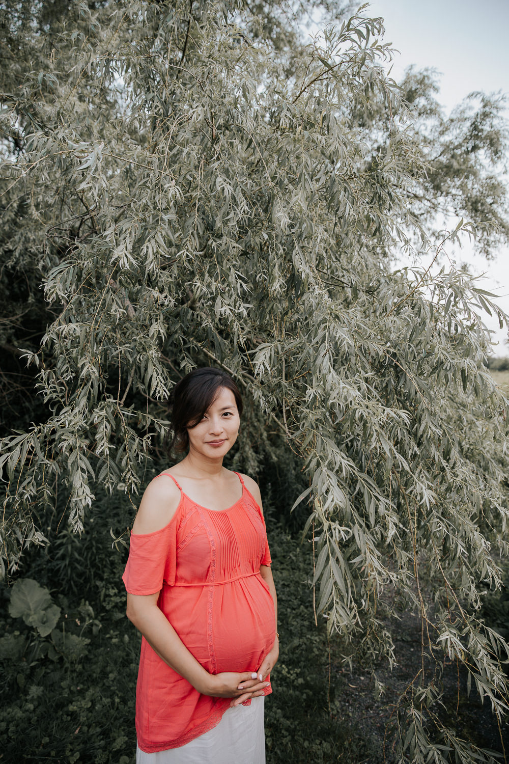 pregnant woman in flowing coral top  and white skirt standing in front of willow tree holding baby belly and smiling softly at camera - Barrie Lifestyle Photos
