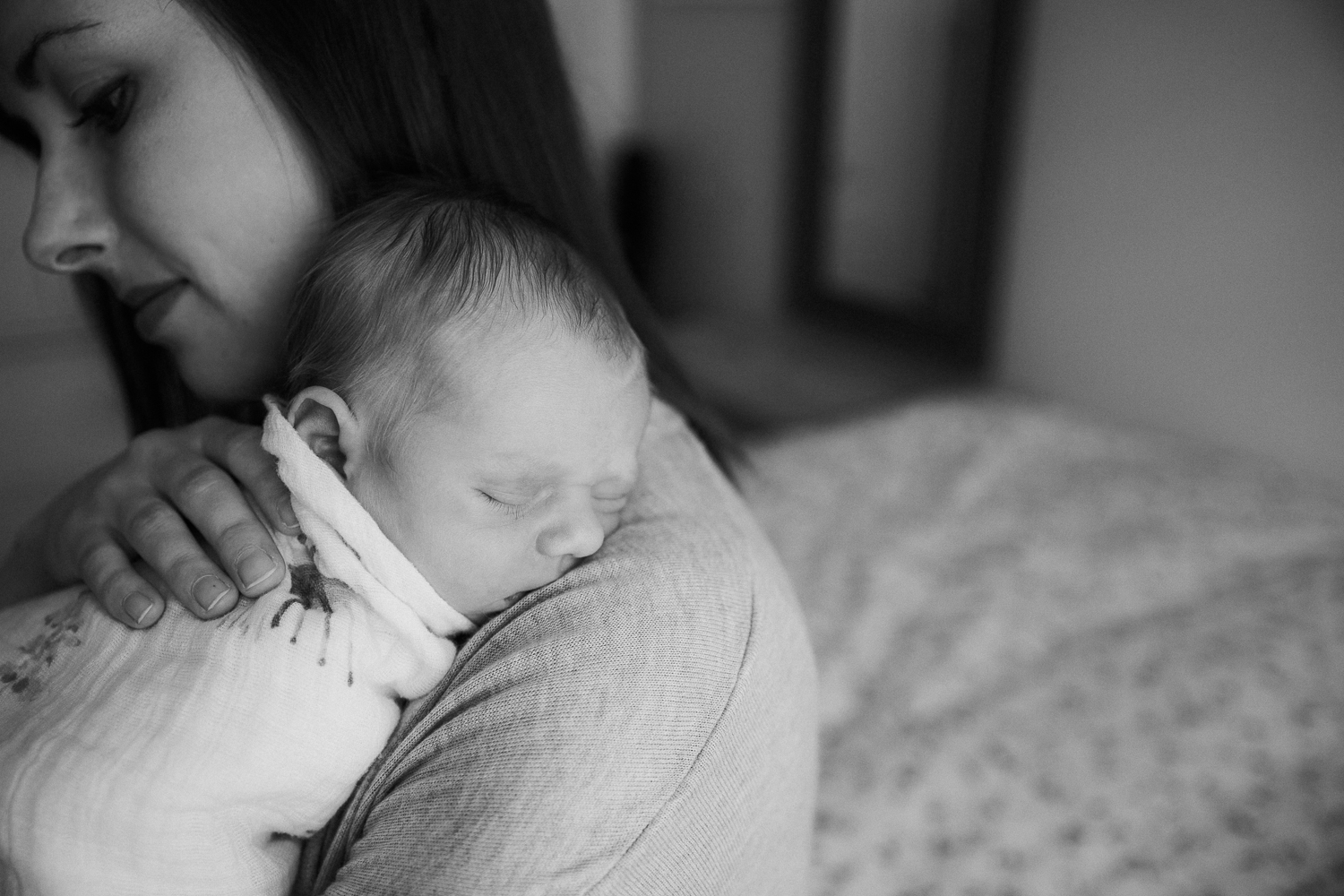 new mom snuggling 3 week old swaddled baby boy to her chest, son's head on her shoulder as he sleeps - Barrie Lifestyle Photography