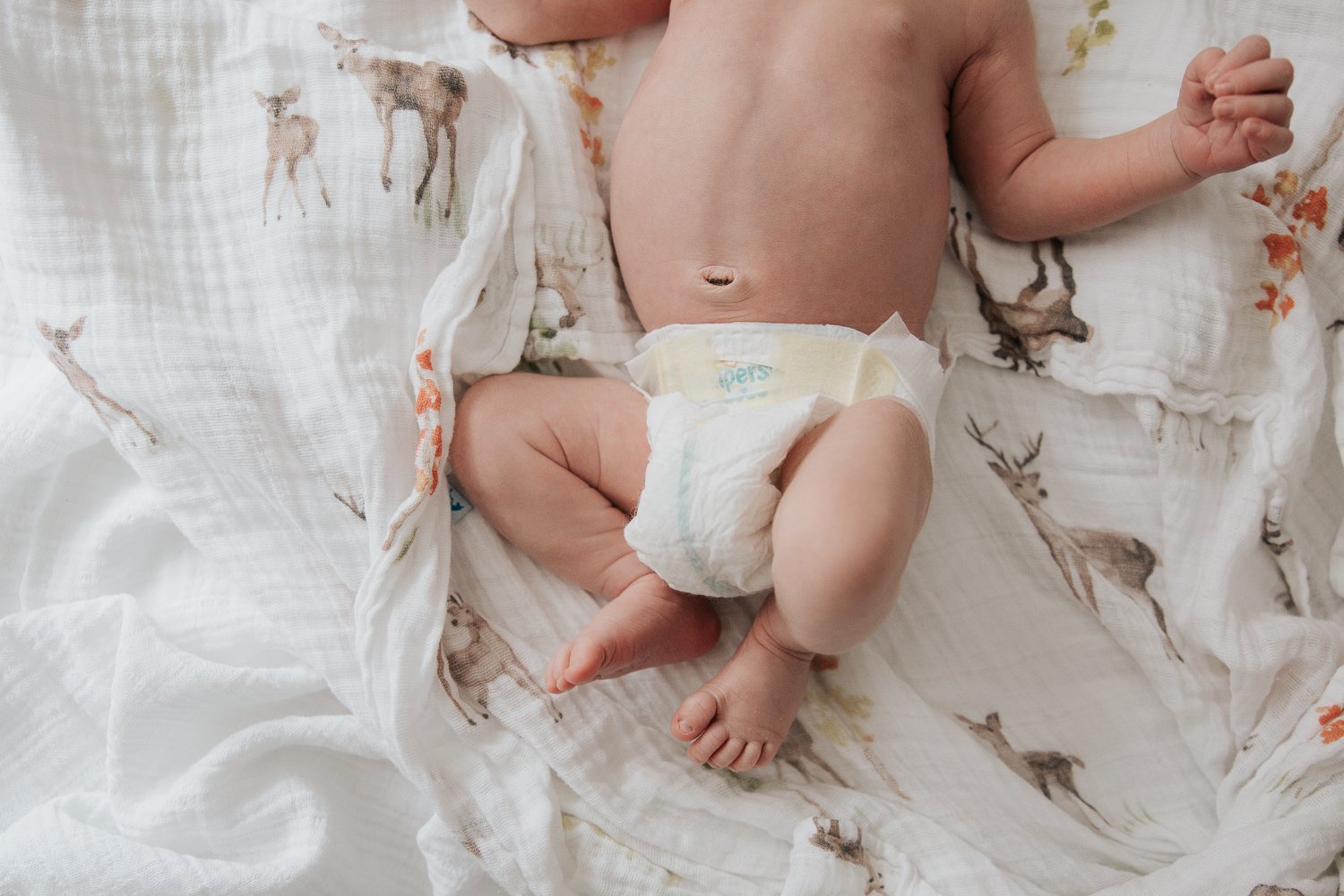 3 week old baby boy in diaper lying on bed, shot of bare bellybutton and feet - Stouffville In-Home Photos