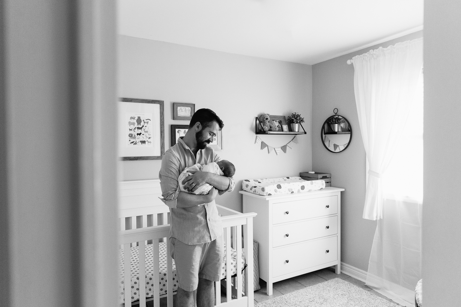 new father with brown hair and beard standing in nursery in front of crib holding 3 week old swaddled baby boy with red hair in his arms and looking at son - GTA In-Home Photos