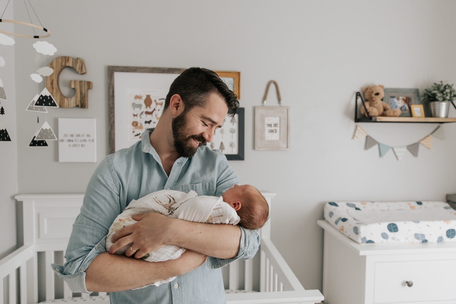 new father with brown hair and beard standing in nursery in front of crib holding 3 week old swaddled baby boy with red hair in his arms and smiling at son - Newmarket Lifestyle Photos