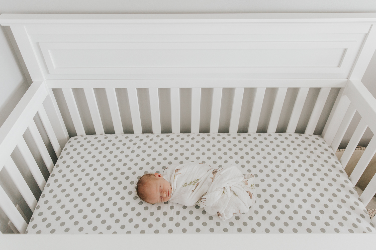 3 week old baby boy with red hair wrapped in swaddle and lying in crib with grey and white polka dot sheets, shot from above - Stouffville Lifestyle Photos