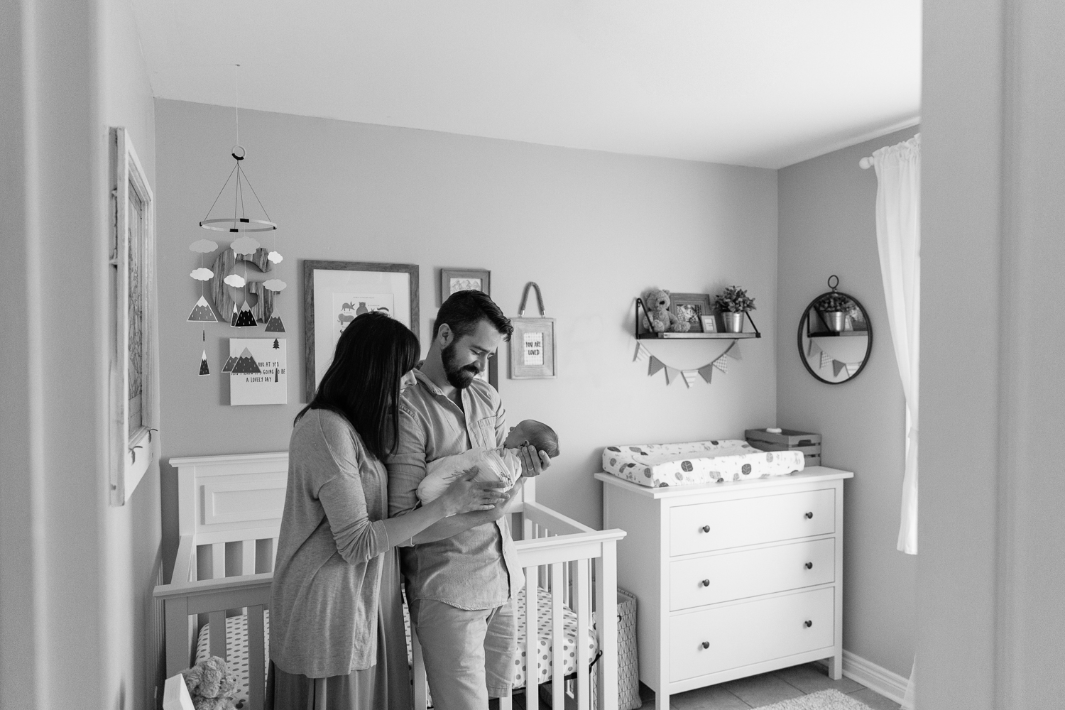 new parents standing in nursery in front of crib, dad holding and looking at swaddled 3 week old baby boy, mom standing next to husband with hand on son - Stouffville Lifestyle Photography