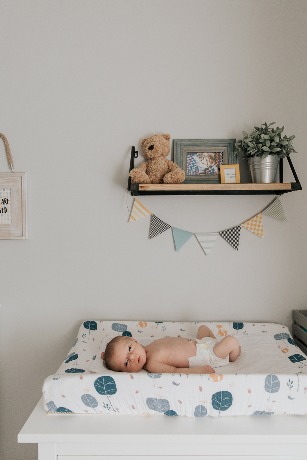3 week old baby boy in diaper with red hair and blue eyes lying on changing table in grey, blue and yellow nursery and looking at camera -Barrie Lifestyle Photos
