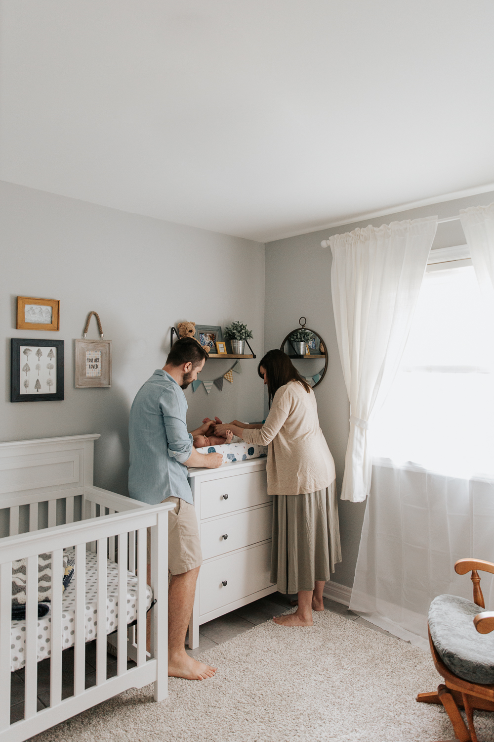 first time parents standing in nursery at change table putting new diaper on 3 week old baby boy -GTA Lifestyle Photos