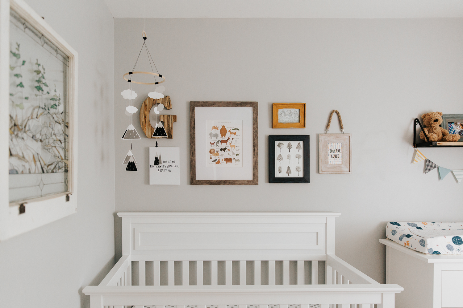 nursery details, grey walls, white crib with a gallery wall containing woodland themed pictures and illustrations - Stouffville Lifestyle Photography