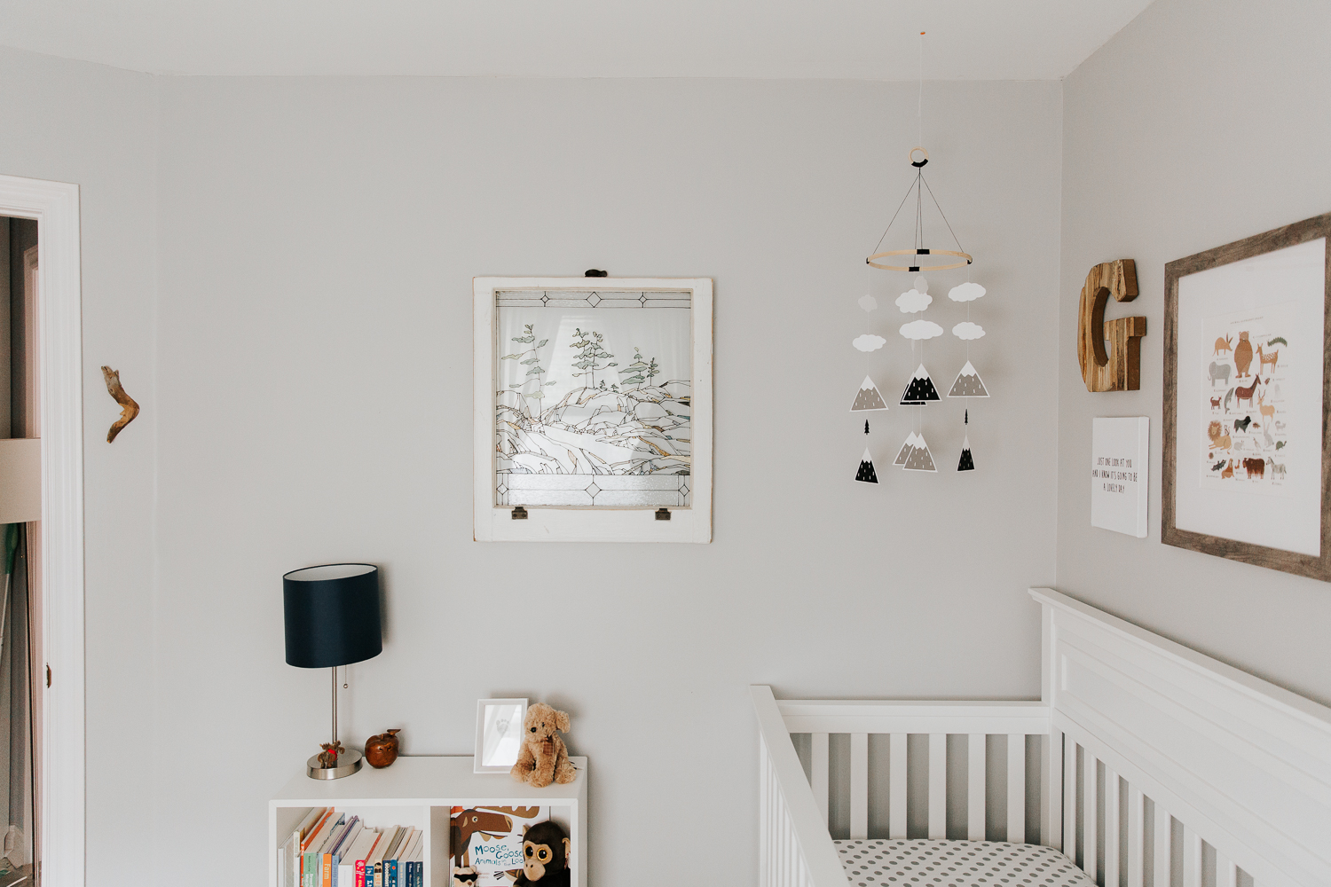 woodland nursery details, grey walls, white crib with a gallery wall, mountain mobile and stained glass window - Markham Lifestyle Photography