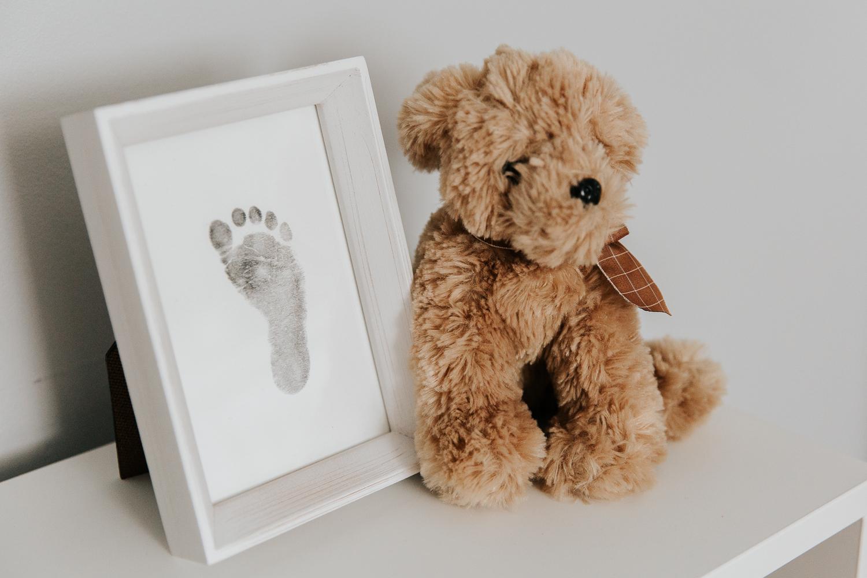 nursery details, stuffed animal dog sitting on shelf next to framed baby footprint - Barrie Lifestyle Photography