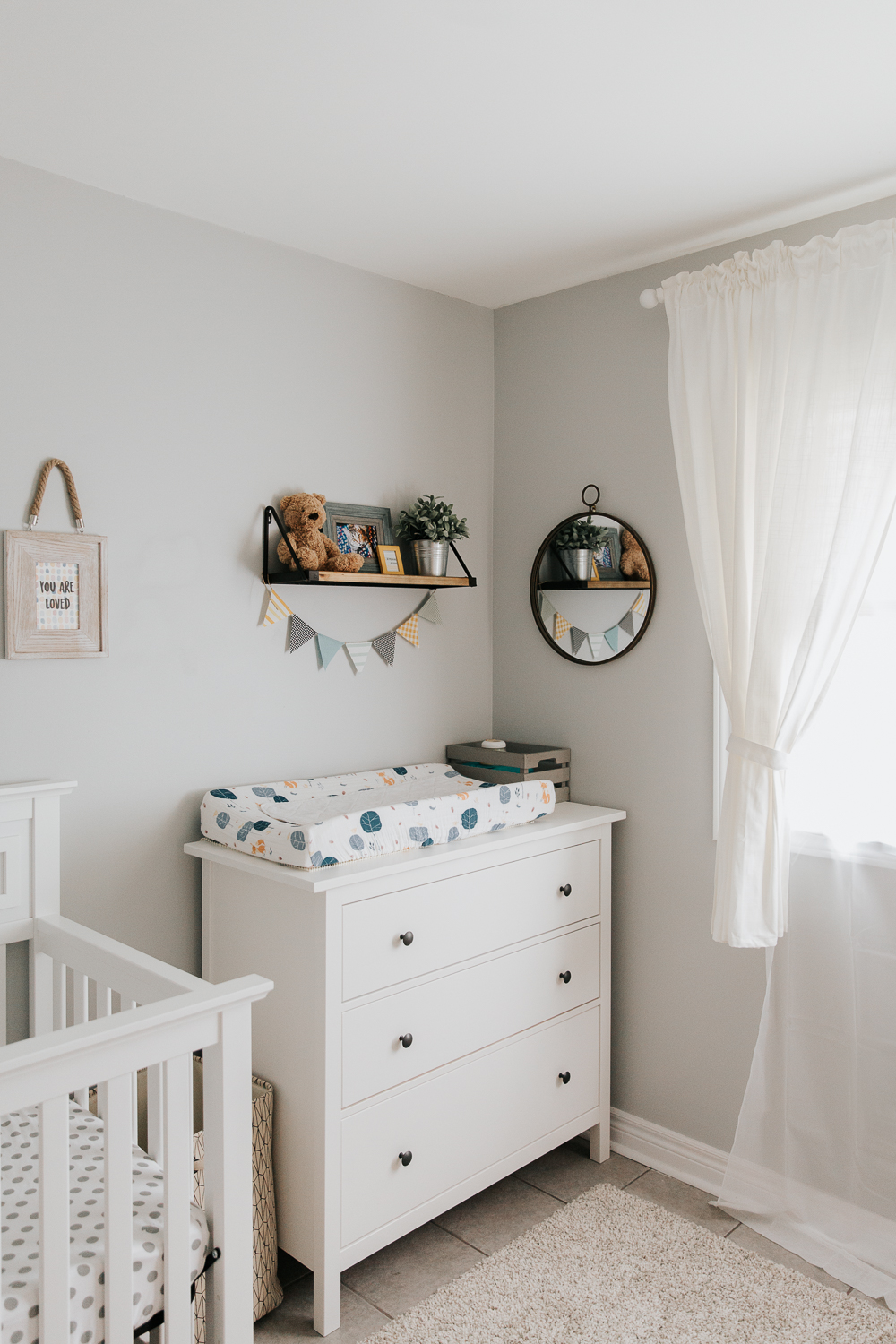 white dresser change table in corner of grey, yellow and blue nursery, wood shelf with bunting hung from it and round mirror on wall -Newmarket In-Home Photography