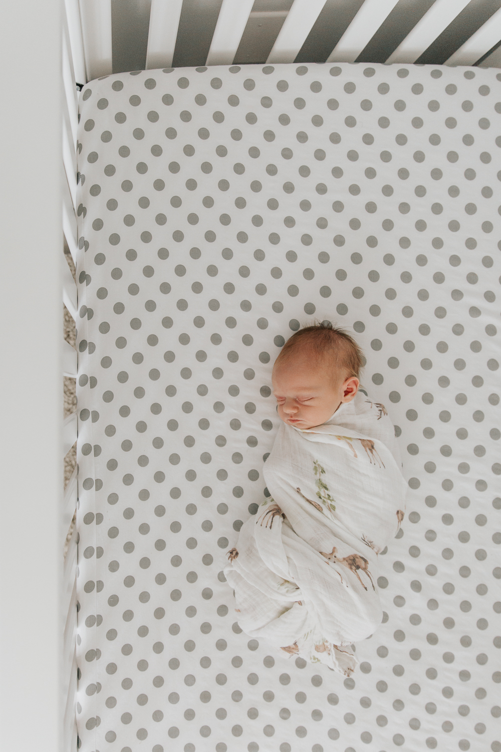 3 week old baby boy with red hair wrapped in swaddle and lying in crib with grey and white polka dot sheets -GTA Lifestyle Photos