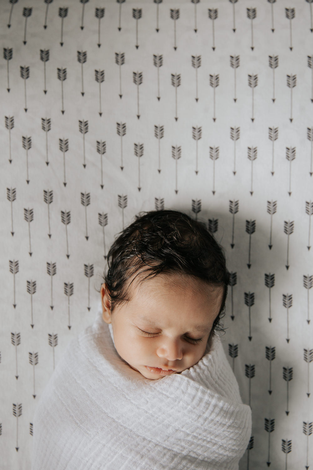 1 month old baby boy with dark hair wrapped in white swaddle lying asleep in crib on black and white arrow patterned sheet, head tilted to one side - Markham Lifestyle Photography