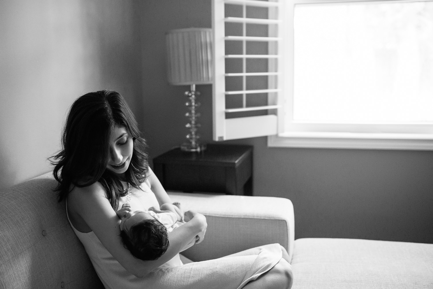 new mom sitting on couch snuggling 1 month old baby boy with dark hair in her arms - GTA Lifestyle Photos