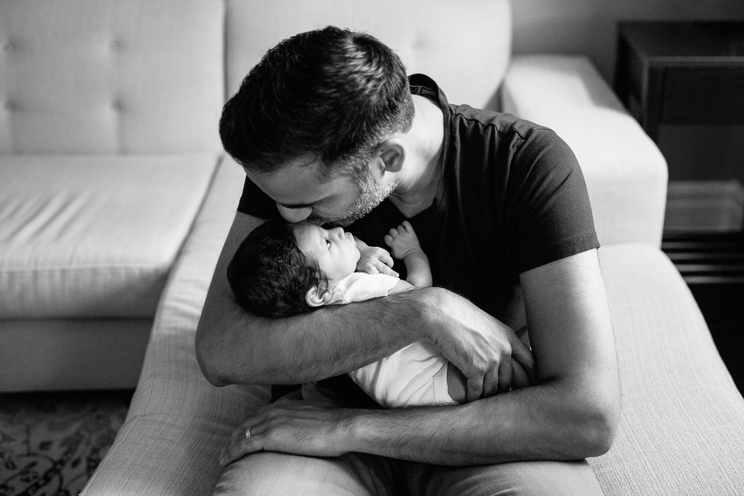 new father sitting on edge of couch holding 1 month old baby boy in onesie in his arms and kissing son on forhead - York Region Lifestyle Photography