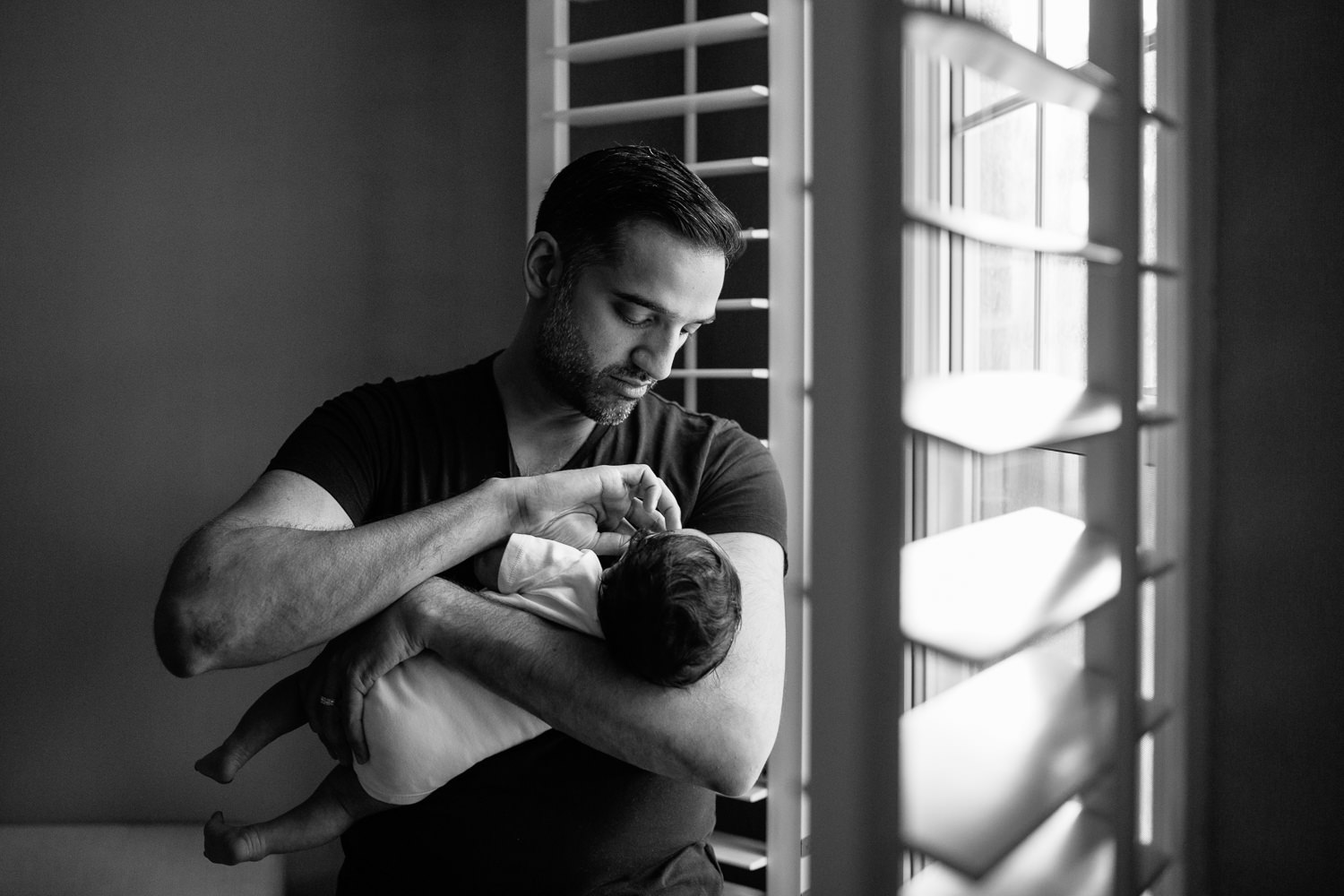 new father standing in front of window holding 1 month old baby boy in onesie in his arms, putting soother in son's mouth - York Region In-Home Photography