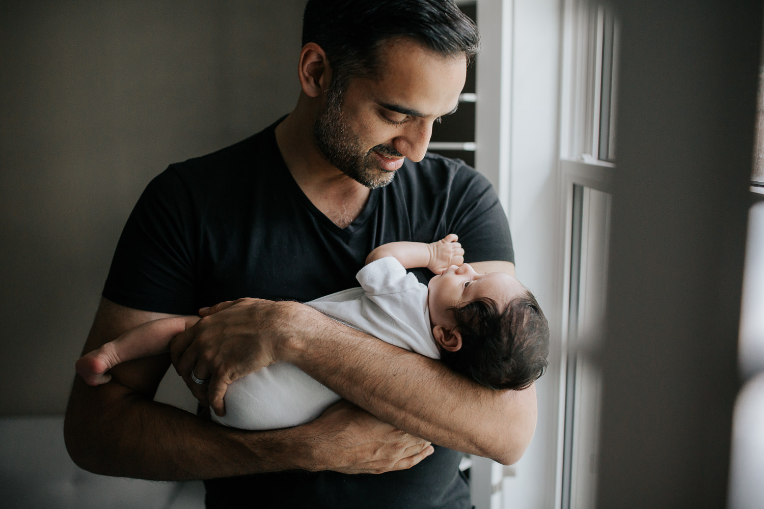 new father standing in front of window holding and smiling at 1 month old baby boy in onesie in his arms - Markham In-Home Photos