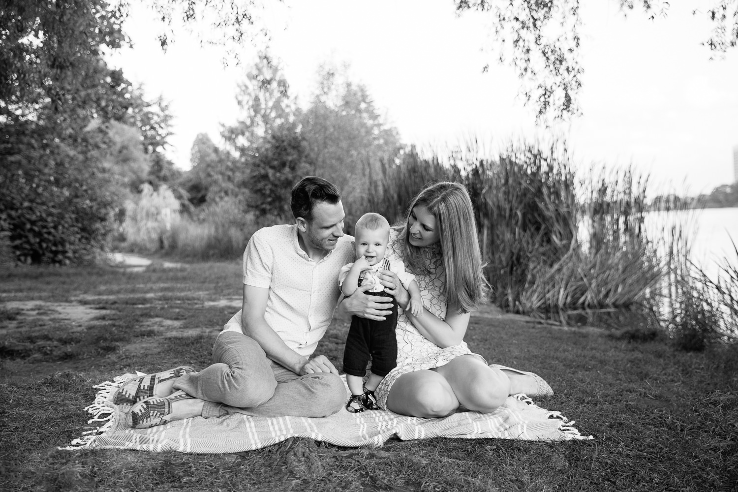 family of 3 sitting on blanket under large willow tree next to pond at high park, 8 month old baby boy standing between mom and dad looking at camera - Barrie Lifestyle Photography