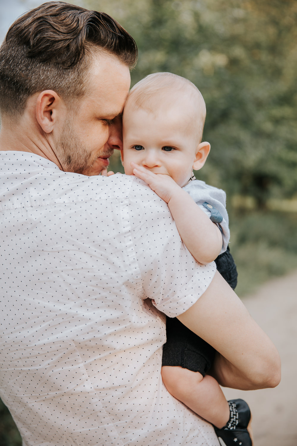 father holding 8 month old blonde baby boy on path at high park surrounded by greenery, dad resting forehead on son's head, baby looking into distance and chewing on hand - GTA In-Home Photos