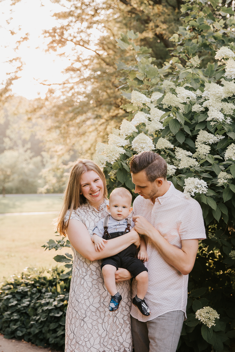 family of 3 standing in high park, setting golden sun behind them, mom carrying 8 month old blonde baby boy and smiling at camera, dad looking at son - Newmarket Lifestyle Photos