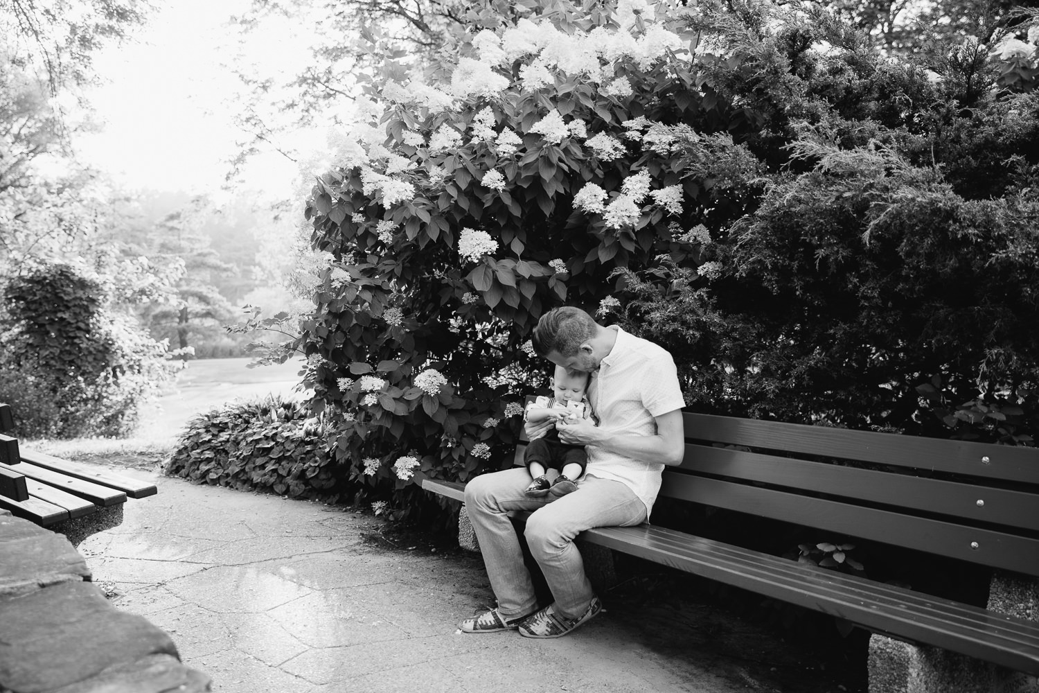 dad sitting on bench in garden at high park with 8 month old blonde baby boy in his lap, snuggling and playing with toy - Markham Lifestyle Photos